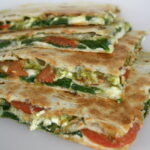 Vegan pesto quesadillas with tomato and spinach cut in half