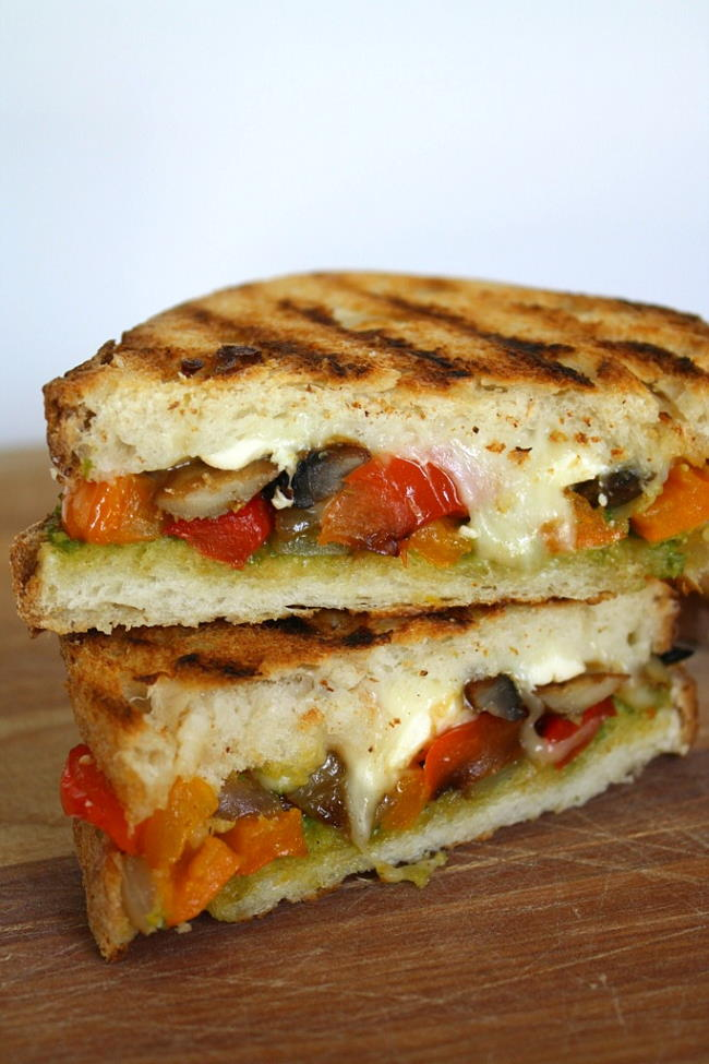 Vegan vegetable pesto panini cut in half on a cutting board