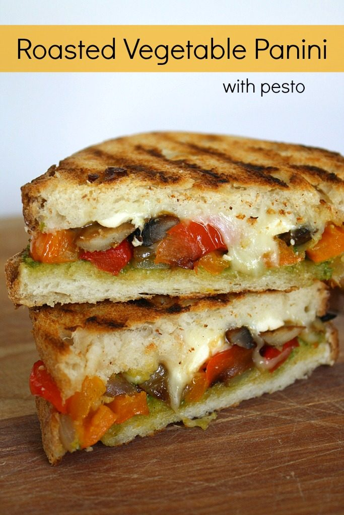 Two halves of roasted vegetable panini stacked on a cutting board