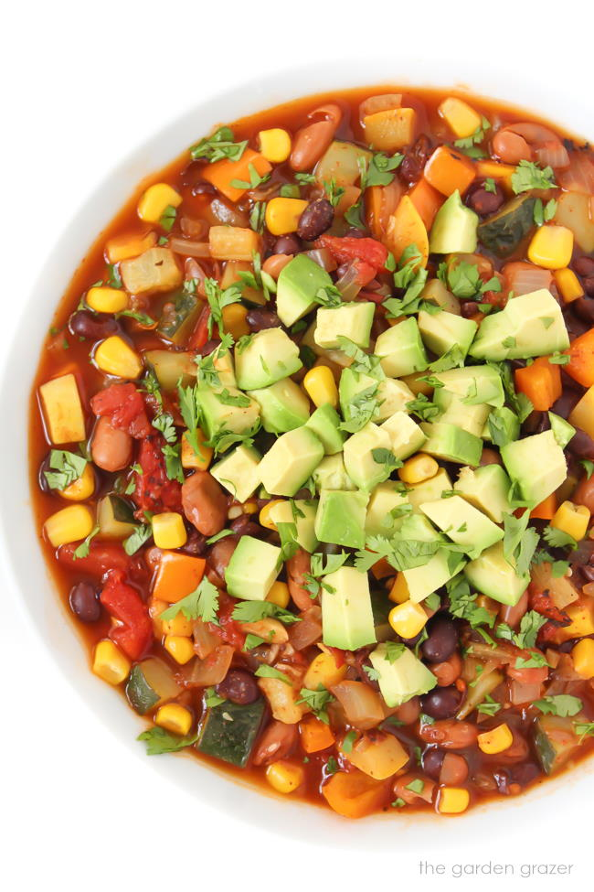Vegan summer vegetable chili in a bowl topped with avocado and cilantro