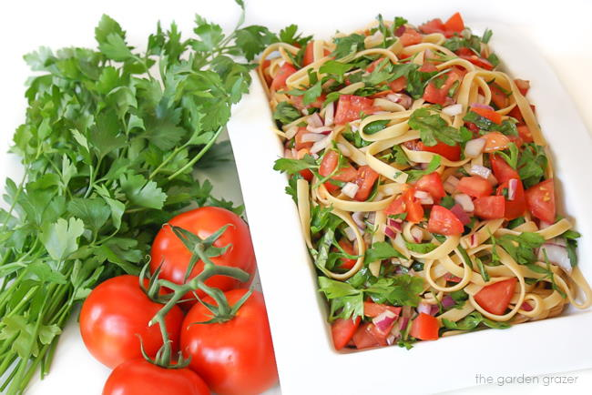 Vegan tomato fettuccine pasta in a white bowl with parsley