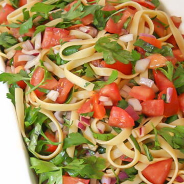 Fresh tomato pasta in a bowl with basil and parsley