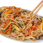 Vegan vegetable lo mein on a plate with chopsticks