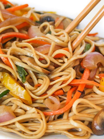 Zoomed-in photo of vegetable lo mein on a plate with chopsticks