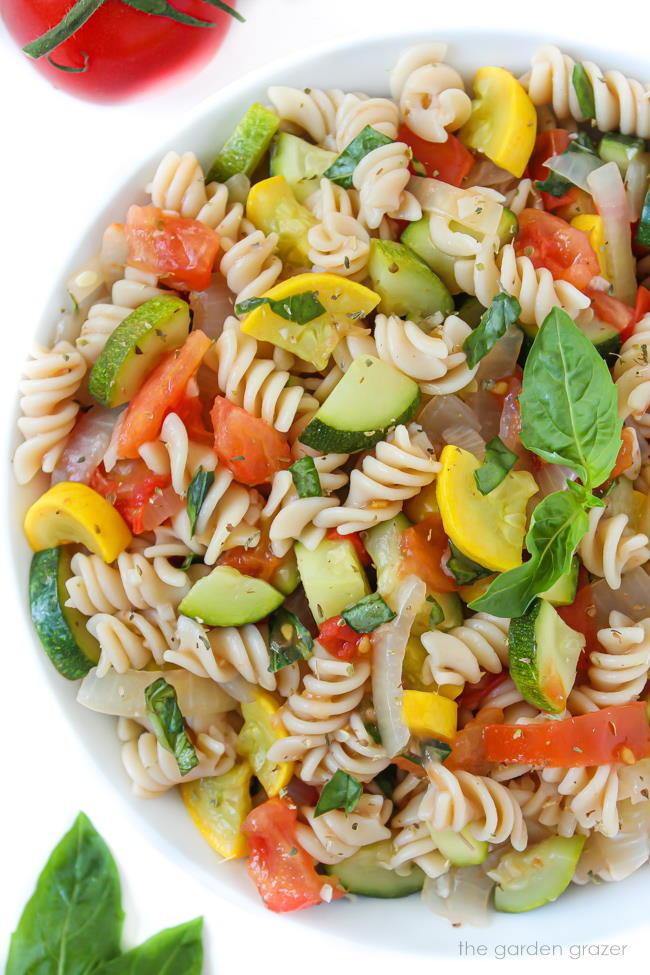 Bowl of fresh garden vegetable pasta with basil
