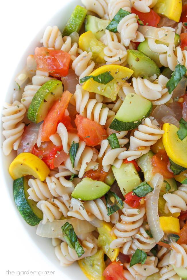 Vegan garden vegetable pasta in a bowl with basil
