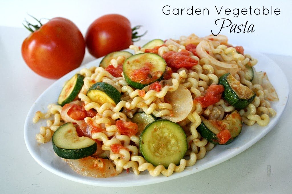 Vegan garden vegetable pasta on a plate with tomatoes