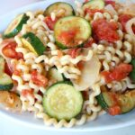 Plate with garden vegetable pasta with zucchini and tomato