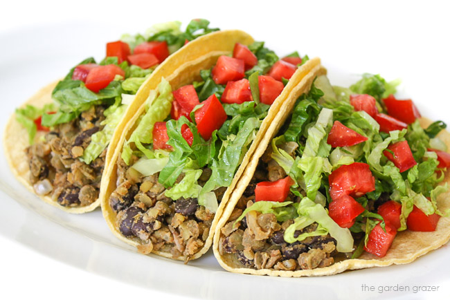 Three black bean and lentil tacos on a plate