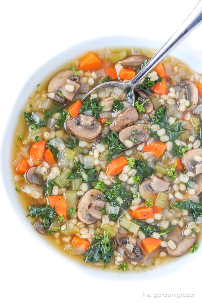 Vegan mushroom barley soup with kale in a bowl with spoon