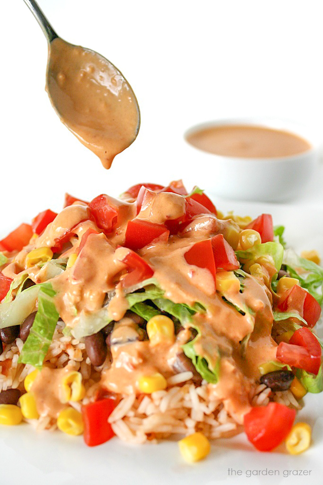 Vegan burrito bowl on a plate being drizzled with chipotle dressing
