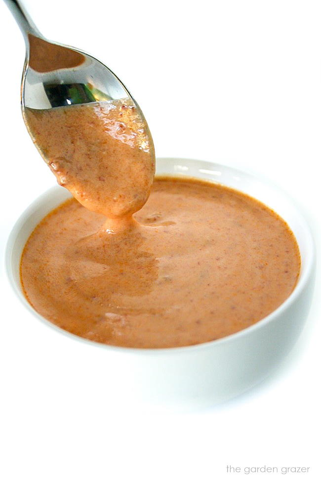 Spoon dipping into a bowl of vegan creamy chipotle sauce