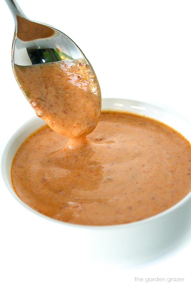Creamy vegan chipotle sauce in a small bowl with spoon