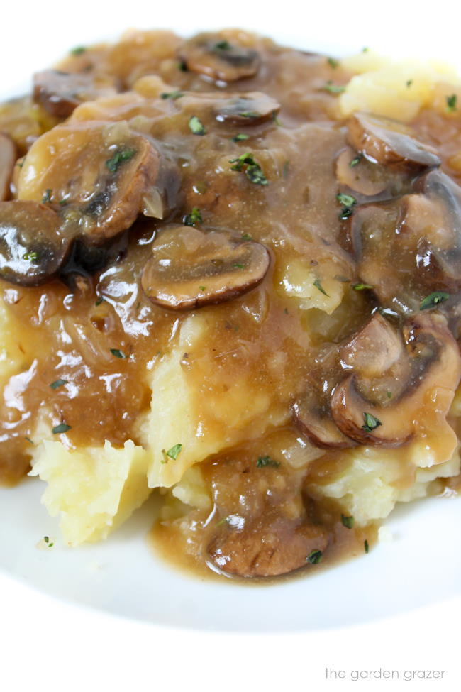Mashed potatoes on a white plate with vegan mushroom gravy on top
