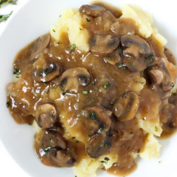 Vegan gravy over mashed potatoes on a white plate