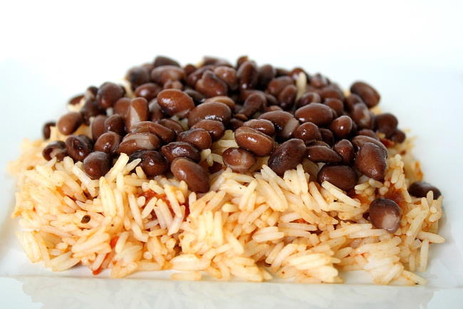 Brown rice topped with black beans on a plate