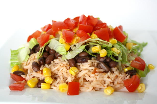 Brown rice, black beans, and fresh vegetables on a plate