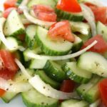 Cucumber salad with onions and tomato on a plate