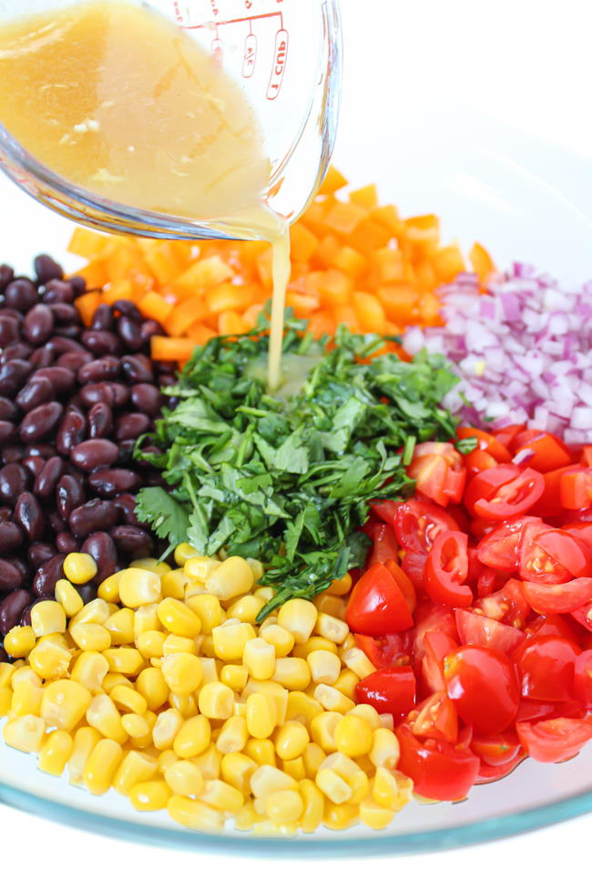 Southwest black bean salad preparation with dressing pouring over top
