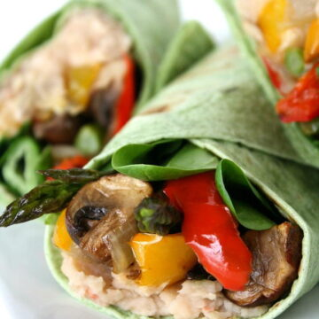 Vegan roasted vegetable wrap with white bean spread on a plate