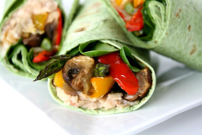 Roasted veggie wraps with white bean spread on a small white plate