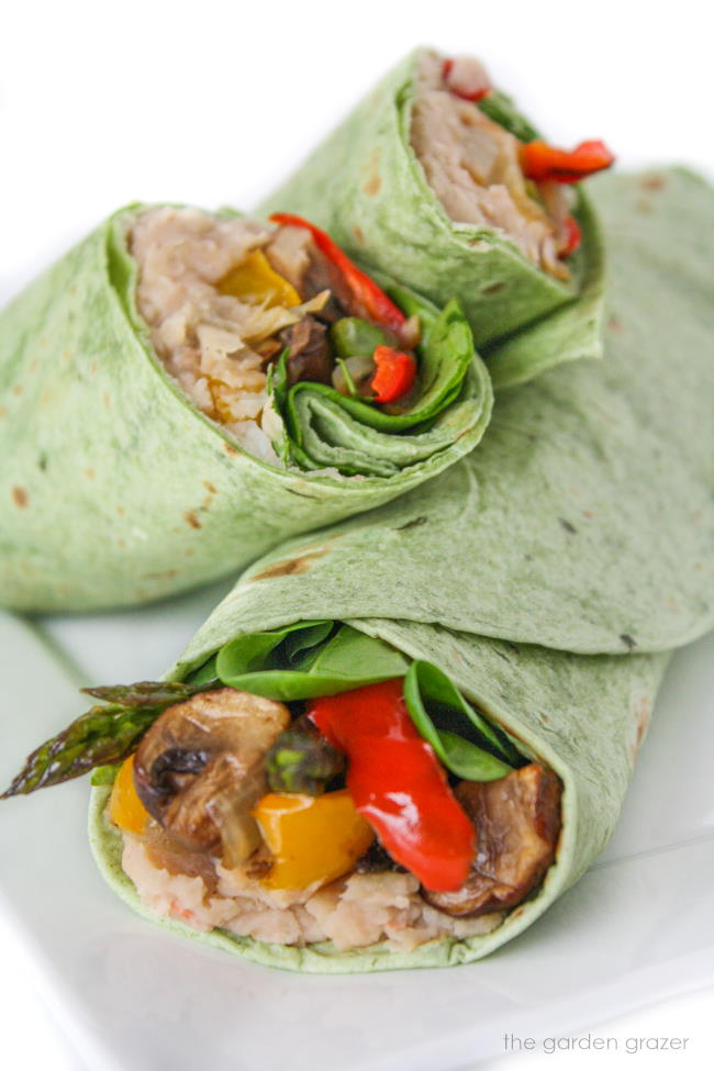 Roasted vegetable wraps cut in half on a white plate