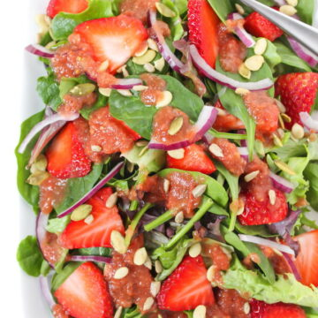 Plate of strawberry spinach salad with tomato balsamic dressing