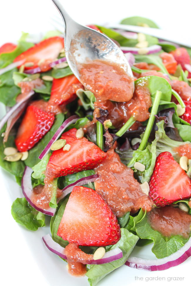 Tomato balsamic dressing being spooned over a spinach salad