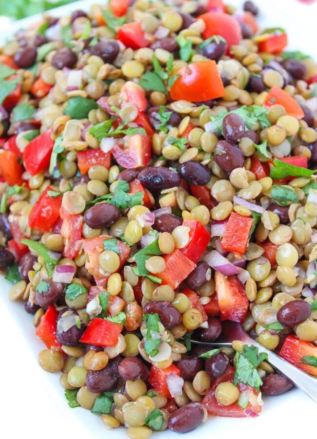plate of vegan black bean lentil salad with tomato and cilantro