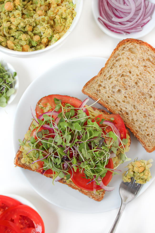 Open-faced sandwich with bread, mashed chickpeas, tomato, and sprouts