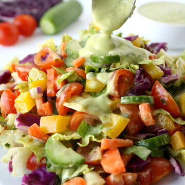 Rainbow chopped salad being topped with avocado dressing