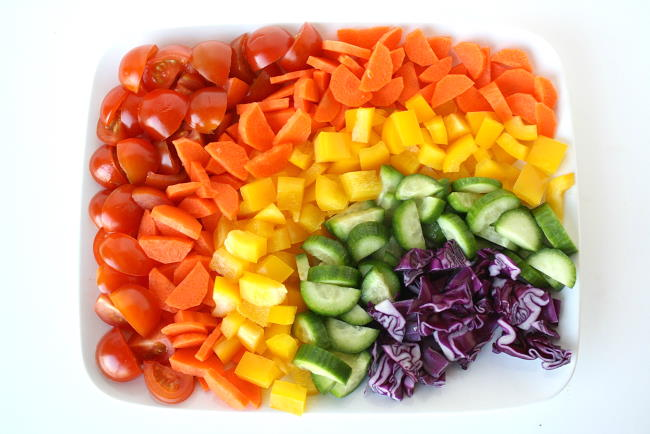Ingredients for rainbow chopped salad arranged on a white plate