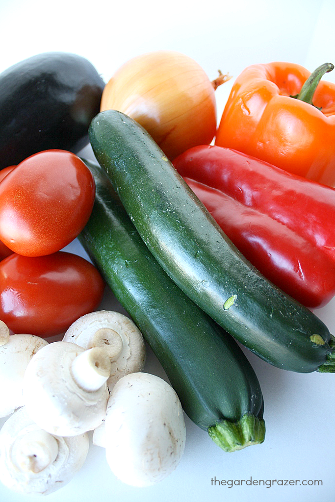 Assorted raw vegetables on a cutting board before roasting