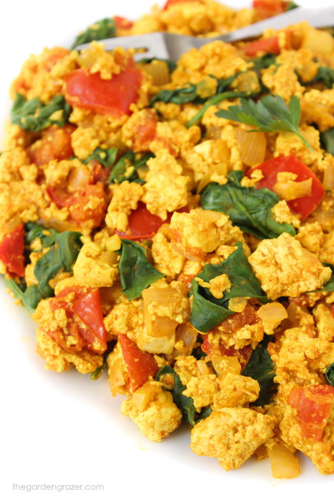 Tofu scramble with spinach and tomato on a plate with fork