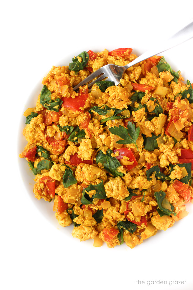 Vegan breakfast scramble with spinach and tomato on a plate