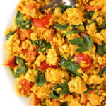 Vegan breakfast tofu scramble with tomato on a plate with fork