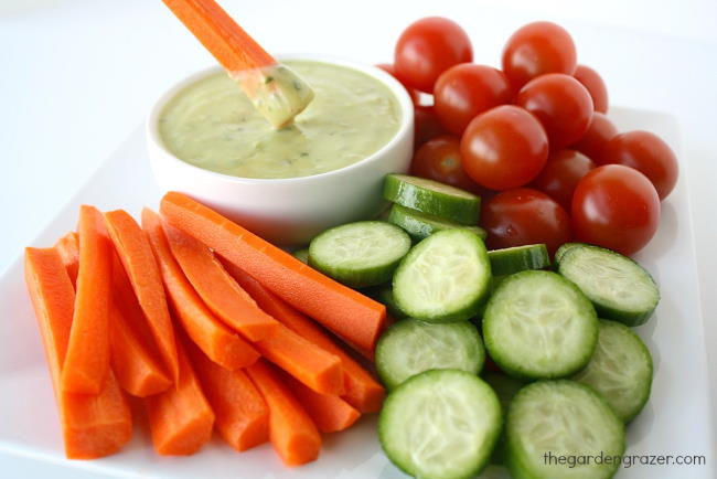 Plate of carrots, cucumbers, and tomatoes with small bowl of creamy avocado dressing