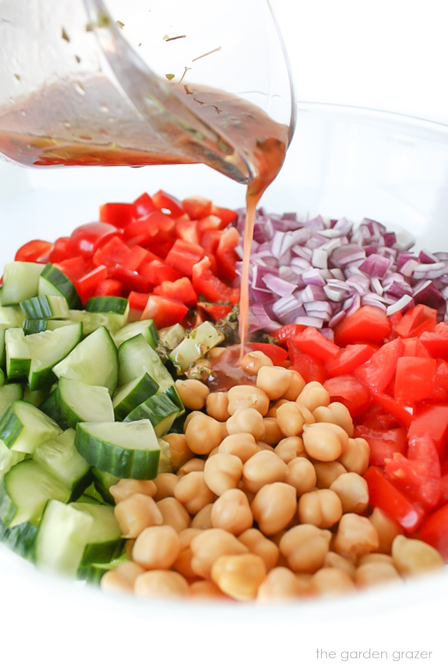 Ingredients for greek chopped salad in a bowl with dressing being poured on top