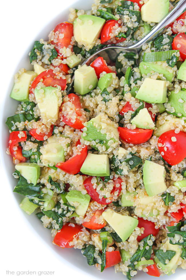 Vegan quinoa avocado salad with spinach and tomatoes in a bowl