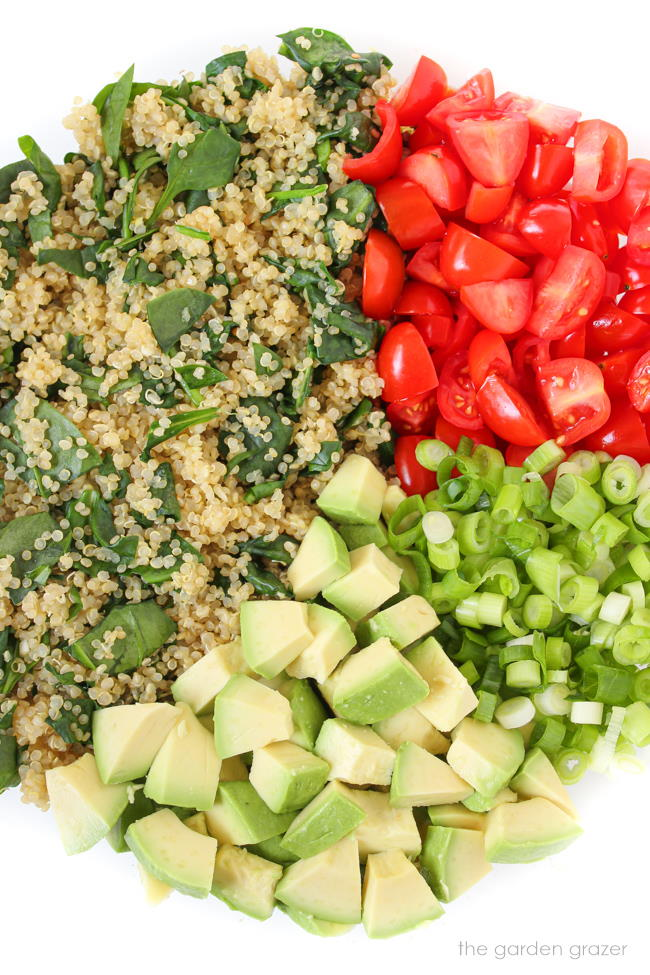 Quinoa avocado salad ingredients in a glass bowl