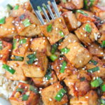 Fork piercing a piece of Asian Style Garlic Tofu from bowl with rice