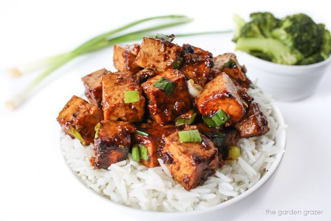 Asian Garlic Tofu in a bowl with white rice and green onions