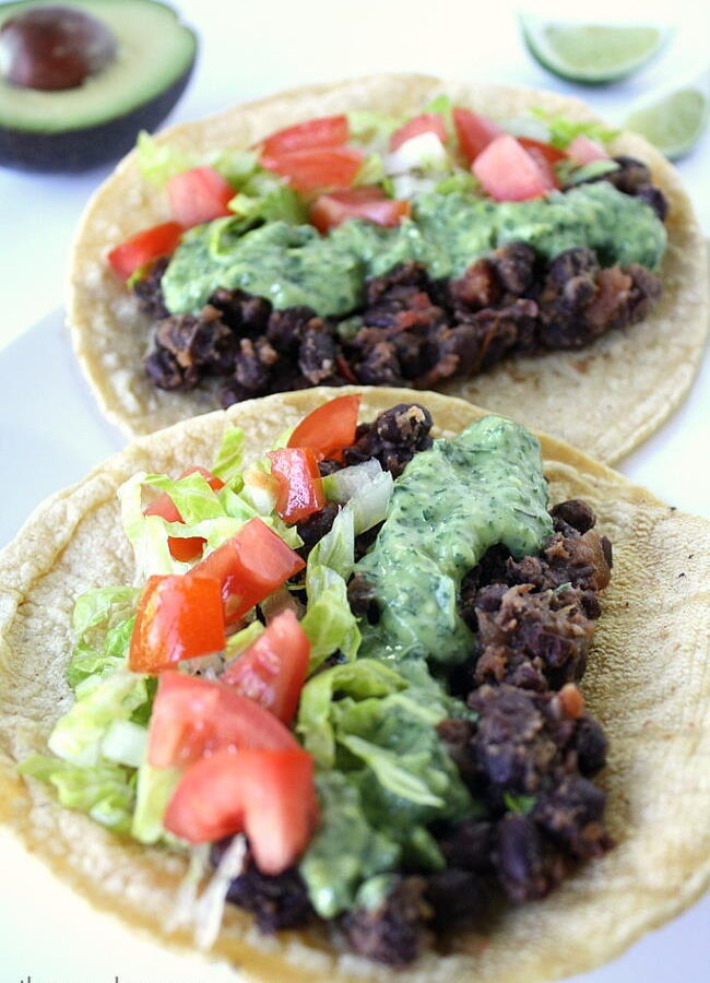 Two black bean tacos on a plate topped with cilantro sauce and tomatoes