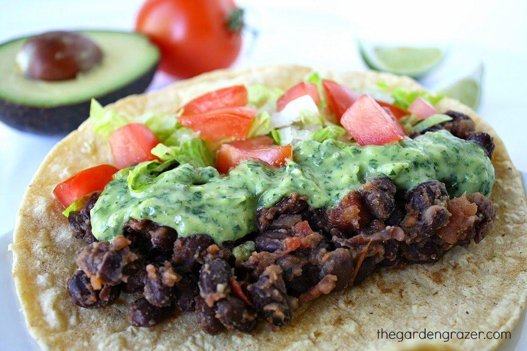Black bean taco topped with avocado sauce