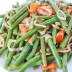 Plate of green beans with tomato and shallot