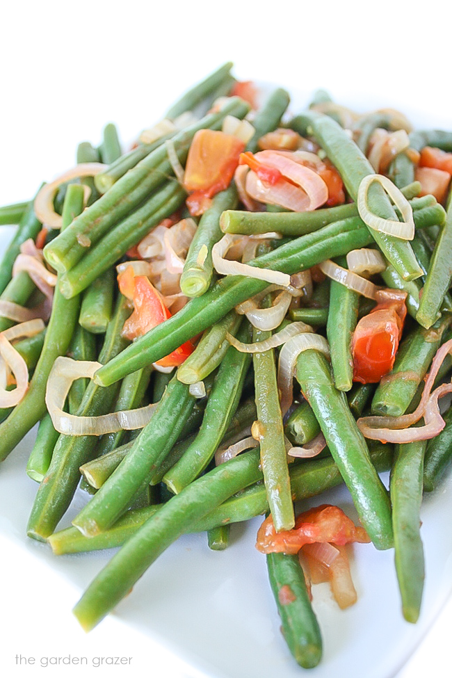 Green beans with shallots and tomatoes on a plate