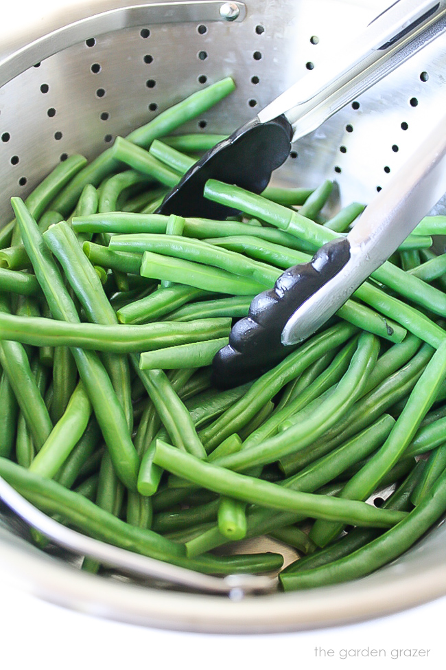 Cooked green beans in a steamer pan