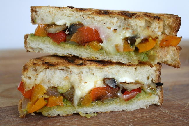 Roasted Vegetable Panini with pesto cut in half on a cutting board