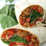 Vegan BBQ tempeh wrap halves on a plate with spinach