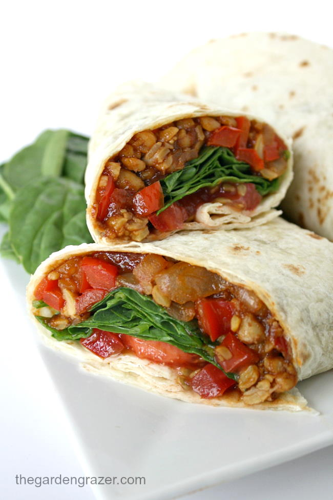 Vegan tempeh wraps with spinach and tomato cut in half on a plate